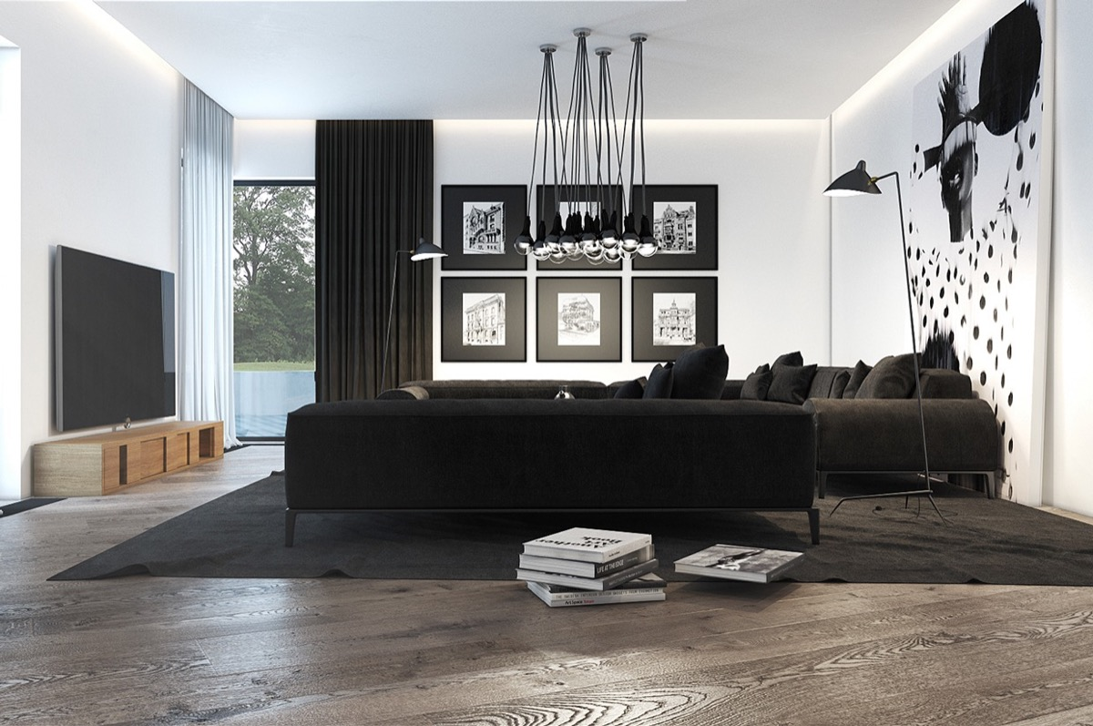 black-modern-living-room-stack-of-books-hanging-lights-large-tv-large-wall-art-picture-frames-black-couches